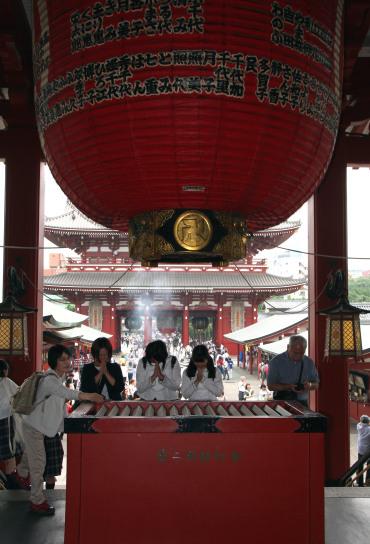 orando Templo Sensoji, Asakusa, Tokio